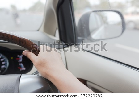 Drivers's hands on a stearing wheel of a car - stock photo