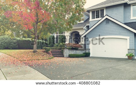 Driveway to front walkway view of partial front of residential home during early autumn season. Light haze effect applied to image.  - stock photo