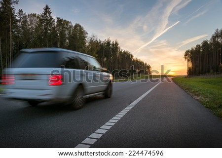 Driving a car on highway at sunset - stock photo