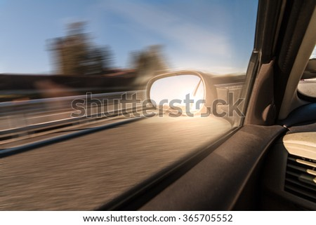 Driving a car on the highway. Speed and freedom concept. Sun flare reflected on rear view mirror. - stock photo