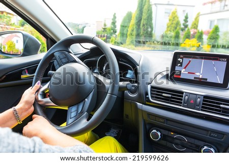 Driving a car with navigation device - stock photo