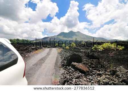 driving across the caldera ridge road among view of extinct crater of the volcano Batur in Bali, Indonesia. - stock photo