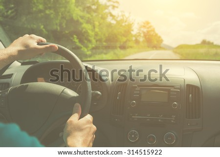 Driving and holding the steering wheel. - stock photo