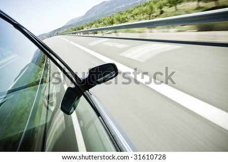 Driving at high speed under blue sky. Angled point of view - stock photo