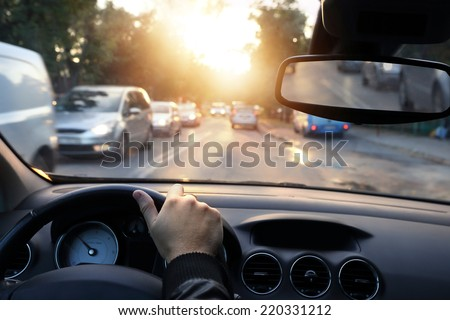 Driving car around town in sunny end of a day - stock photo