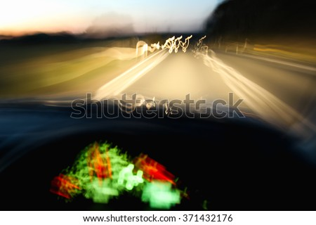 Driving car dangerously at night due to drinking, speeding or being tired - stock photo