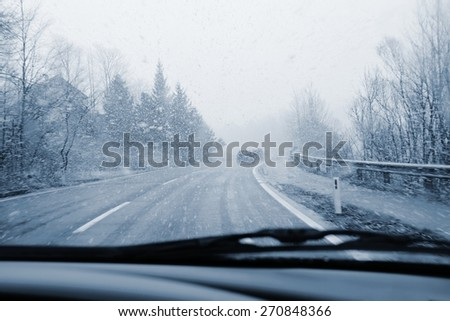 Driving from the driver's perspective in bad weather in the snow - stock photo
