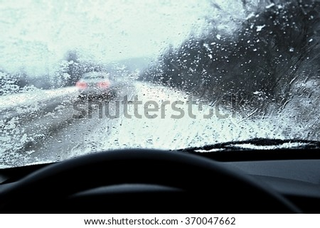 Driving from the driver's perspective in bad weather in the snow and rain. - stock photo