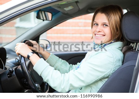 Driving happy woman holding steering wheel