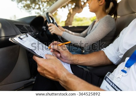 driving instructor inside a car with student driver doing checklist - stock photo