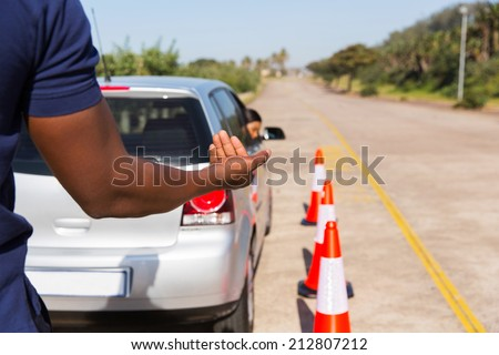 driving instructor teaching young girl to reverse - stock photo
