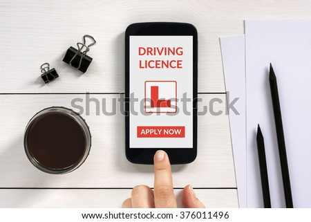 Driving licence app mock up on smart phone screen with office objects on white wooden table. All screen content is designed by me. - stock photo