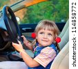 Driving little girl. Beautiful cheerful baby  in a car - stock photo