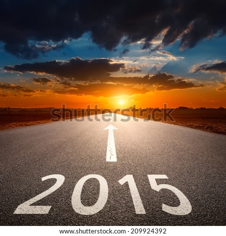 Driving on an empty asphalt road at sunset forward to upcoming new year - stock photo