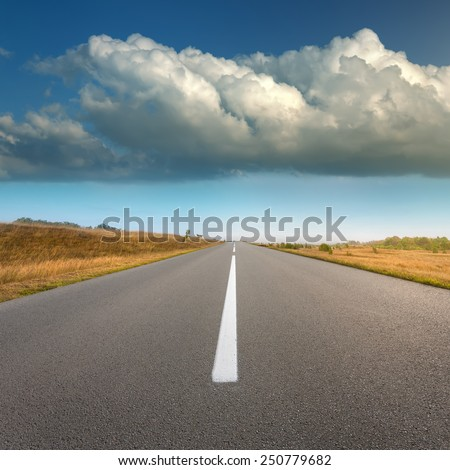 Driving on an empty asphalt road through the idyllic fields at sunny day, against the big threatening cloud. - stock photo