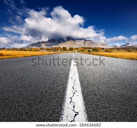Driving on an empty asphalt road to the mountains at sunny day - stock photo