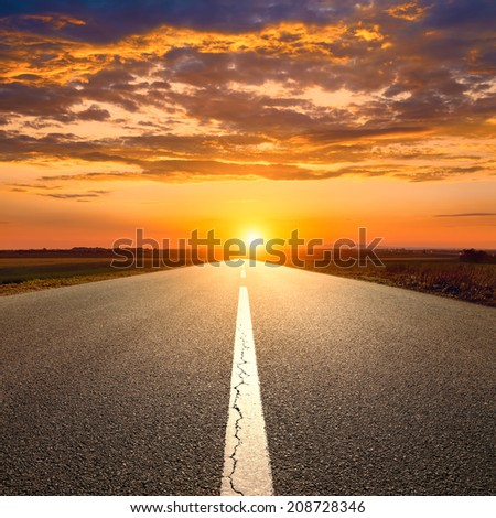 Driving on an empty asphalt road towards the sunset