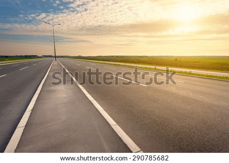 Driving on an empty asphalt six lane highway through the cultivated fields towards the setting sun. - stock photo