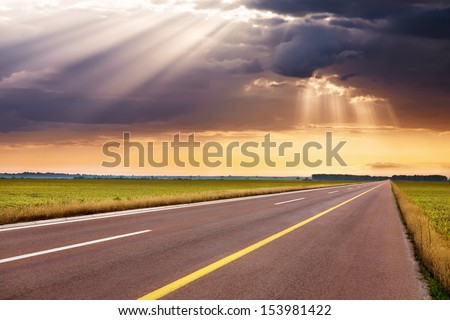 Driving on an empty highway to the oncoming storm - stock photo