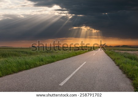 Driving on an empty open road towards the big unusual sunbeams - stock photo