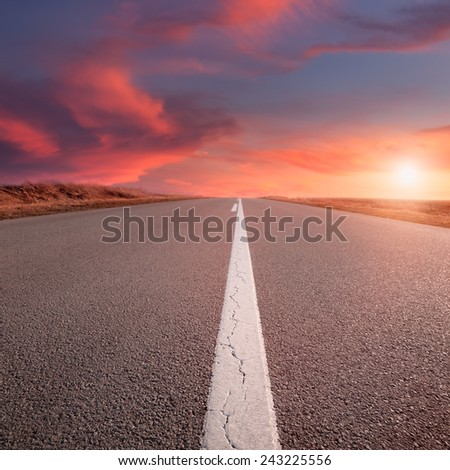 Driving on an empty road at sunset. Focus on the beginning of the asphalt road