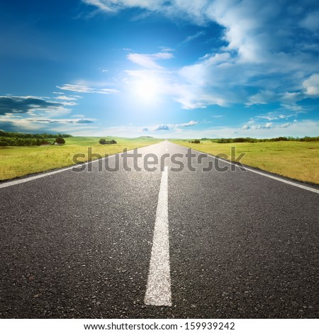 Driving on an empty road to the sun - stock photo