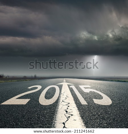 Driving on an empty road towards the lighting storm to upcoming 2015 - stock photo