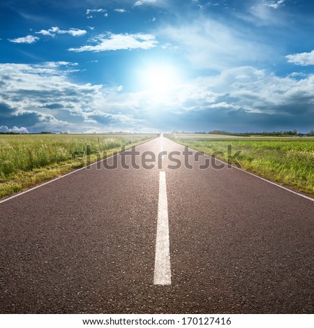 Driving on an empty road towards the sun - stock photo