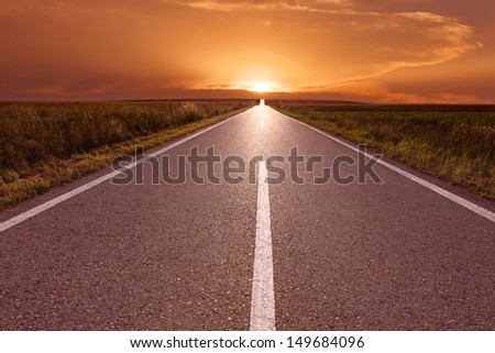 Driving on empty road at red sunset