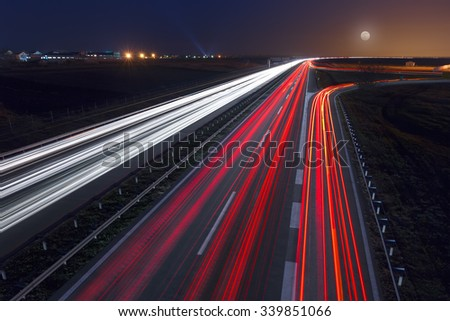 Driving on highway at night near Belgrade - Serbia. Light trails on motorway at night of full moon, long exposure abstract photograph. - stock photo