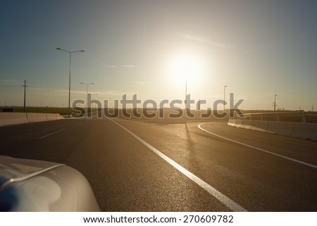 Driving on the highway near exit from the motorway towards the setting sun. Drive by. - stock photo