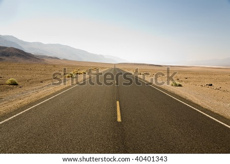 driving on the Interstate 187 in Death valley direction Badwater in the heat of the Mojave Desert - stock photo