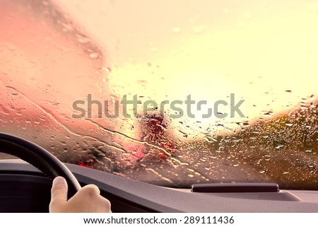 Driving onto a Highway at Sunset. Rainy weather rush hour traffic jam scene - poor view caused by heavy rain and  back light - stock photo