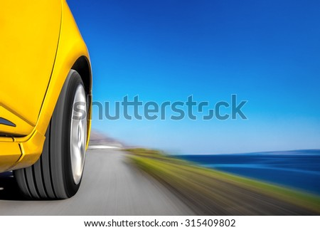 Driving sports car fast on the road by the sea