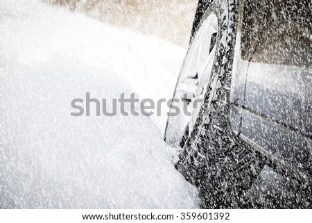 Driving SUV car in winter on forest road with much snow - stock photo