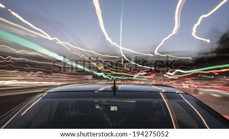 driving through Munich, during night/dusk/twilight, rigged camera on the rear/trunk of a german black car, bulb exposure - time-lapse, special effects photography - stock photo