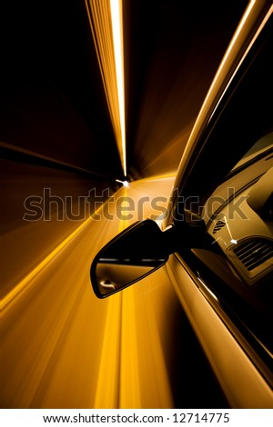 driving through tunnel with motion blur - focus on mirror - stock photo