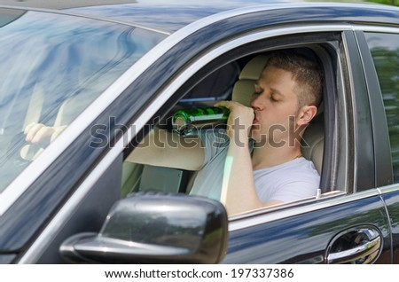 Driving Under the Influence. Man drinking alcohol in the car. - stock photo