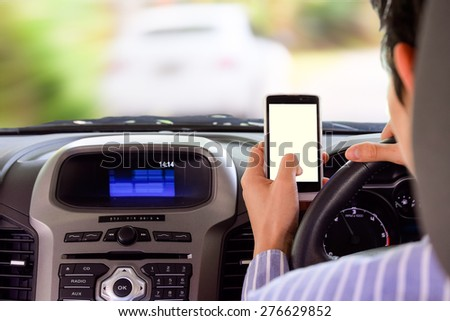 Driving while holding a mobile phone (cell phone use while driving) - stock photo