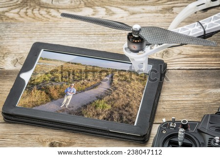 drone aerial photography concept - reviewing aerial picture (drone operator in a field) on a digital tablet with a drone rotor and radio control transmitter, - stock photo