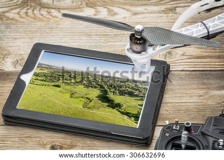 drone aerial photography concept - reviewing aerial picture of Colorado foothills near Fort Collins  on a digital tablet with a drone rotor and radio control transmitter, - stock photo