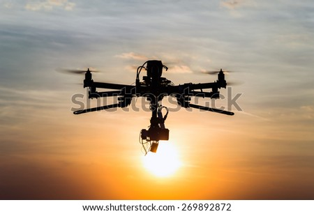 Drone flying in the sunset - stock photo