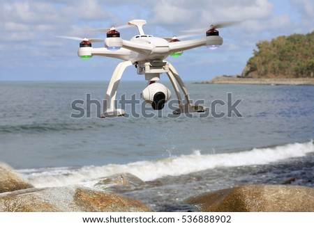 drone with camera flying over the sea