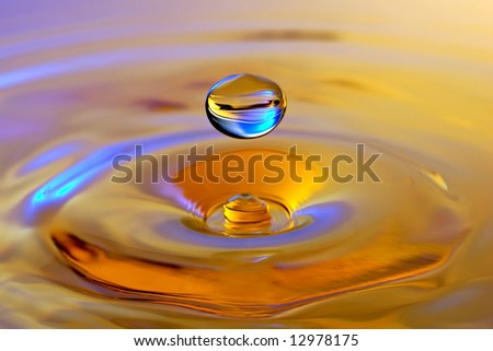 Drop falling into water in shades of gold and blue - stock photo