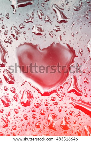 Drop in the form of heart on wet glass with red glow