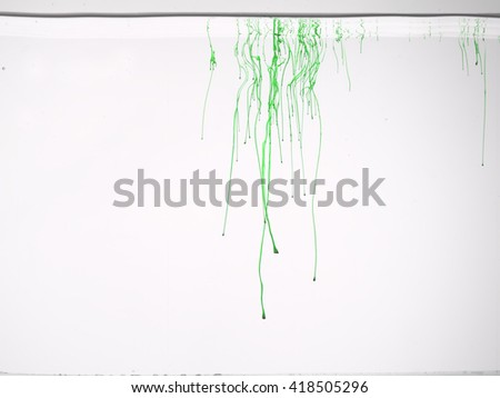 Drop of green color in water, isolated on white background.  - stock photo