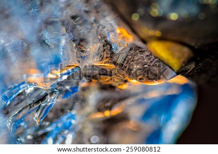 Drop of melting ice water at the drainpipe, with reflections of blue sky and yellow sun rays passing through. Macro with ice structure seen through the drop of water. - stock photo