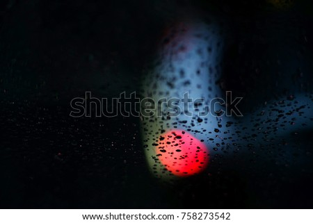 drop of rain on glass with bokeh in the night