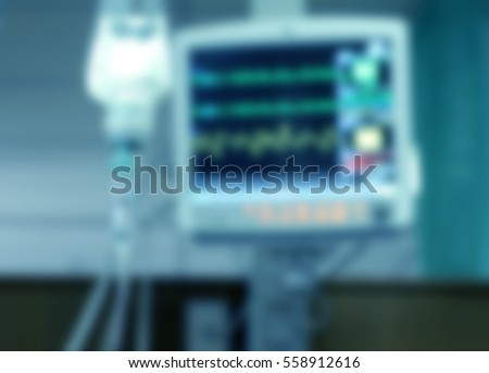 Drop of saline solution to help patient and medical monitors in a hospital, blurred background.