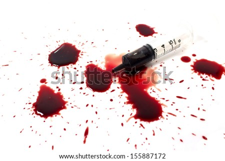 Drops of blood and a syringe on a white background.